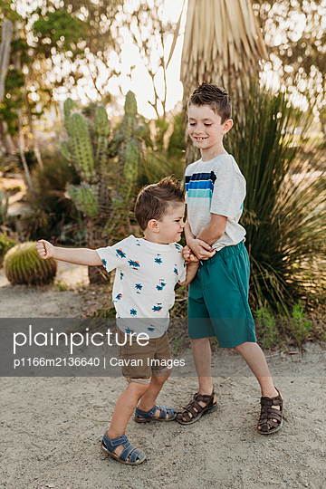 Full body view of young toddler brother playing with older brother - p1166m2136640 by Cavan Images
