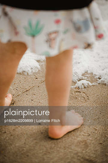 Little girl on the beach close to wave - p1628m2209899 by Lorraine Fitch