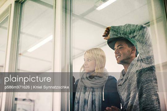 Junges Paar schaut aus dem Fenster - p586m971626 von Kniel Synnatzschke