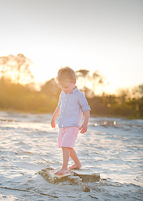 Boy standing on rocks at beach against sky during sunset - p1166m1566821 by Cavan Social