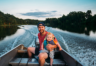 Portrait of father with son sitting in motorboat on lake - p1166m1577207 by Cavan Images