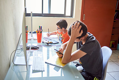 Two boys (8-9, 14-15) learning at desk at home during Covid-19 lockdown - p1427m2235626 by Francisco Navarro