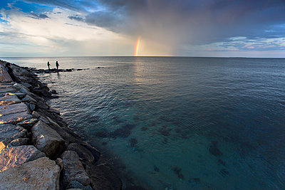 Rainbow and cloudy sky over silhouettes of two people fishing on coastal rocks, Massachusetts, USA - p343m1500357 by Jess McGlothlin Media