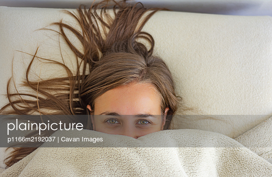 Woman in bed covered up to the face - p1166m2192037 by Cavan Images