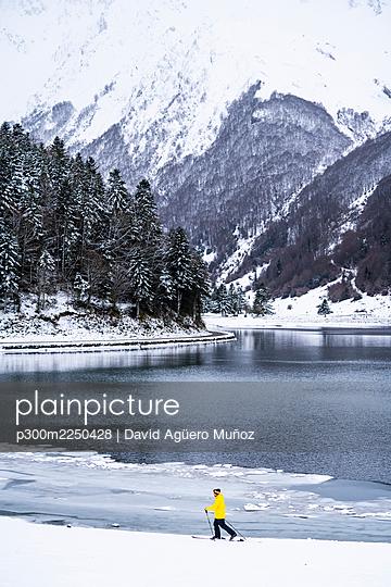 Man skiing at snow covered lakeshore - p300m2250428 by David Agüero Muñoz