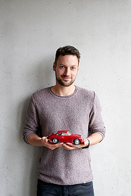 Man holding toy car in hands - p1124m1511040 by Willing-Holtz