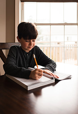 Young boy doing schoolwork in a workbook at home at the table. - p1166m2174189 by Cavan Images