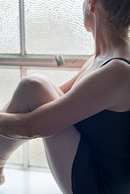 A ballerina sits on the window sill of a dance studio. - p1433m2019988 by Wolf Kettler