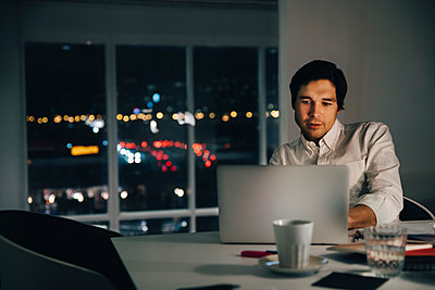 Confident businessman using laptop while sitting at desk in creative workplace - p426m2194750 by Maskot