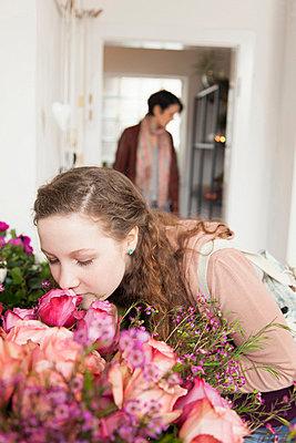 Teenage girl smelling bouquet in florists - p429m802981f by Stefanie Grewel