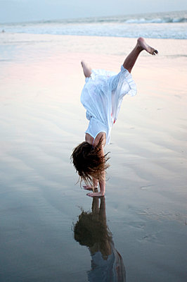 Puerto Vallarta, Mexico; Girl doing a cartwheel on the beach - p4429583f by Design Pics