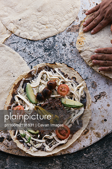 Overhead of tlayuda and tortilla cooking on open comal in Mexico - p1166m2191831 by Cavan Images