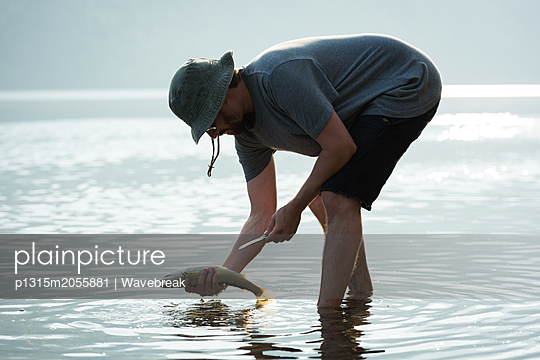 Fisherman holding a fish near riverside - p1315m2055881 by Wavebreak