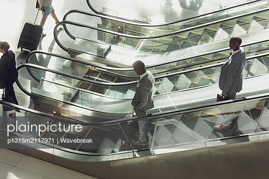 Business people using escalators in modern office  - p1315m2117971 by Wavebreak