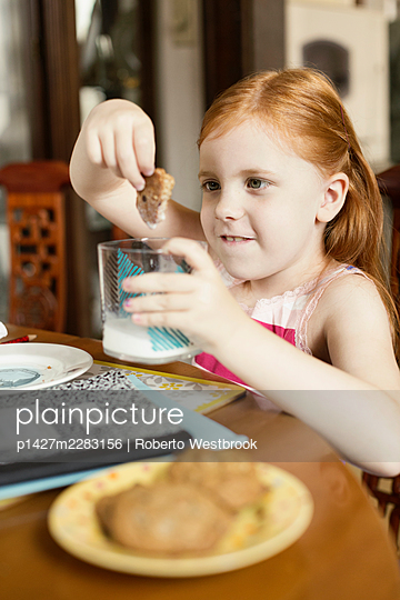 Girl dipping biscuit into glass of milk at dining room table - p1427m2283156 by Roberto Westbrook