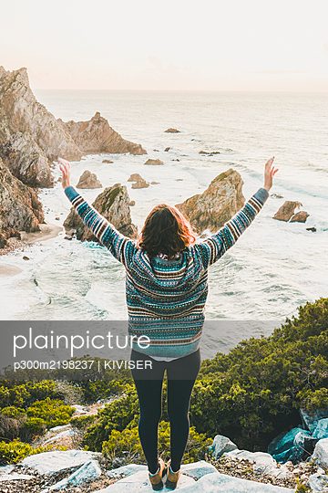 Young woman standing arms outstretched on rock at Ursa Beach, Lisboa Region, Portugal - p300m2198237 by KIVISER