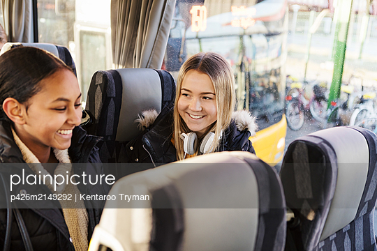 Smiling female friends traveling together in bus at city - p426m2149292 by Kentaroo Tryman