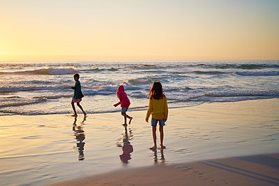 Brother and sisters running in ocean surf at sunset - p1023m2200821 by Trevor Adeline