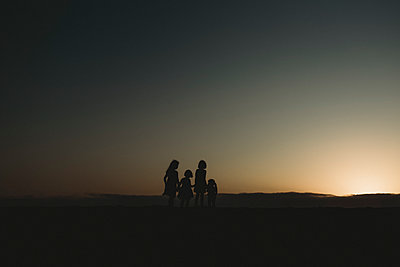 Silhouette of four young sisters at beach during sunset - p1166m2165908 by Cavan Images
