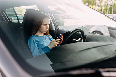 Serious woman holding her smart phone while sitting inside the car. - p1166m2171653 by Cavan Images