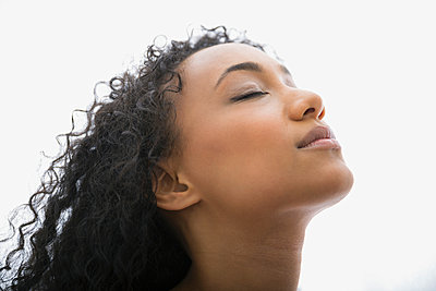 Serene woman with head back and eyes closed - p1192m1014198f by Hero Images