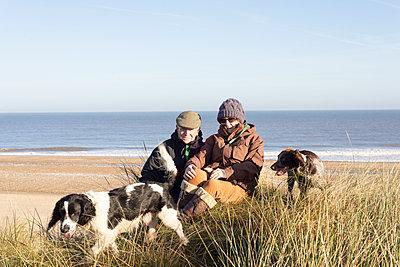 Ehepaar mit Hunden am Strand - p1201m1538658 von Paul Abbitt