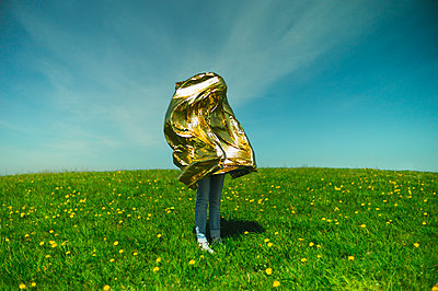 Woman hidden under golden thermal blanket - p1551m2199960 by André Eikmeyer