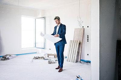 Architect holding blueprint in building under construction - p300m2005462 von Robijn Page