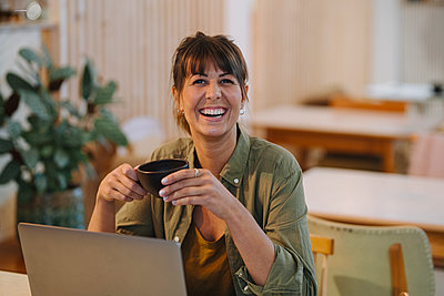 Female owner laughing while holding coffee cup using laptop in cafe - p300m2225856 by Gustafsson