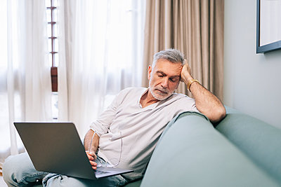Exhausted man with laptop sitting on sofa in hotel room - p300m2250687 by Daniel González