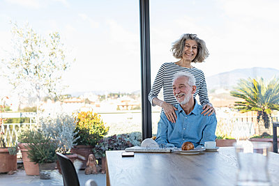 Happy woman standing behind smiling man at home - p300m2265843 by Emma Innocenti