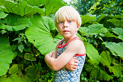 Blonde boy standing by green leaves - p312m1549176 by Scandinav Images