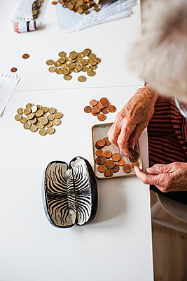 Woman counting coins - p312m2140043 by Anna Johnsson