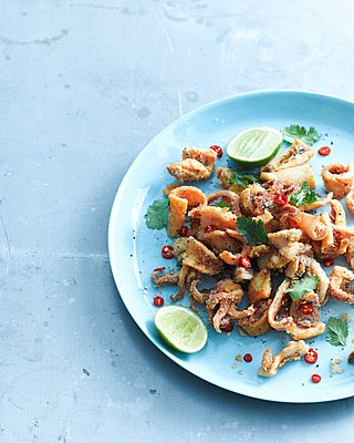 Overhead view of salt and pepper chilli squid garnished with lemon and coriander on plate - p429m1125964f by BRETT STEVENS