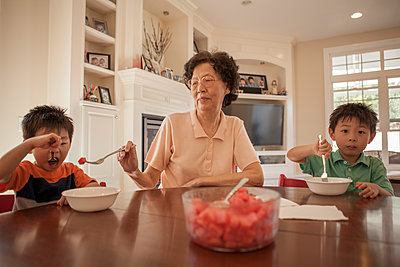 Asian grandmother feeding grandsons at table - p555m1408701 by Shestock