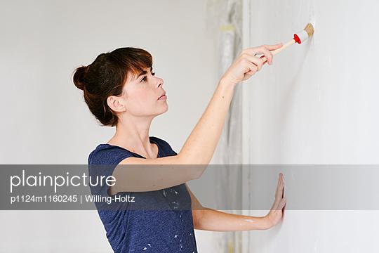 Junge Frau beim Streichen - p1124m1160245 von Willing-Holtz