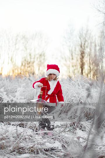 Girl wearing Santa clothes at winter - p312m2092202 by Lisa  Öberg