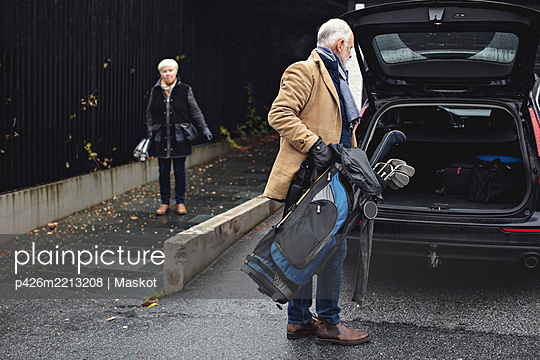 Senior man holding golf bag by car trunk while female partner standing on sidewalk during winter - p426m2213208 by Maskot