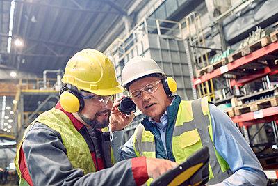 Steelworkers wearing ear protectors using digital tablet in steel mill - p1023m1519946 by Agnieszka Olek