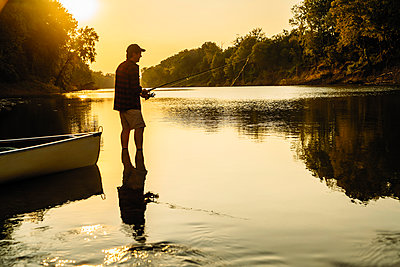 Side view of mid adult man fishing while standing in lake during sunset - p1166m1524917 by Cavan Images