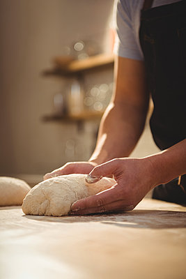 Chef kneading dough in professional kitchen - p1315m1422003 by Wavebreak