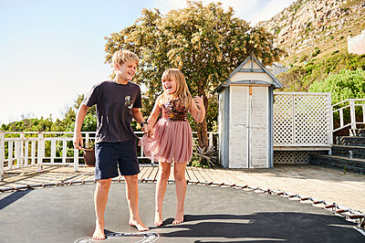 Two children standing on trampoline - p1640m2244884 by Holly & John