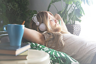 Man with long hair and beard lying on sofa listening music with headphones - p300m1470147 by Retales Botijero