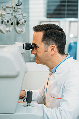 Male optometrist looking phoropter in clinic - p300m2243867 by Manu Padilla Photo