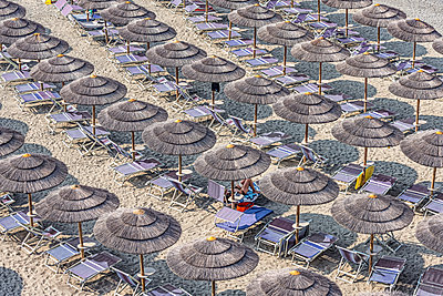 Straw beach umbrellas and lounge chairs on tourist resort beach, Varazze, Liguria, Italy - p301m2148979 by Niels Schubert