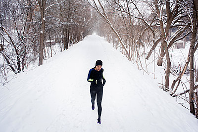 Young female runner in knit hat running in snow covered tree lined park - p429m1408036 by Hugh Whitaker