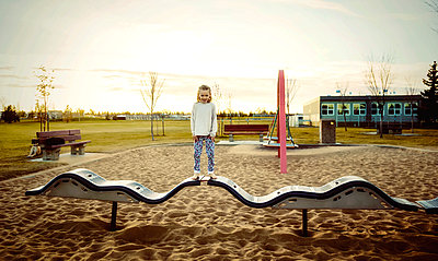 A young girl posing for the camera while standing on a bouncing balance beam in a playground on a warm autumn evening at sunset; Edmonton, Alberta, Canada - p442m2012185 by LJM Photo