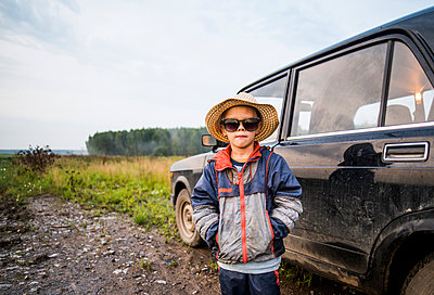 Caucasian boy standing near car in rural field - p555m1420566 by Aleksander Rubtsov