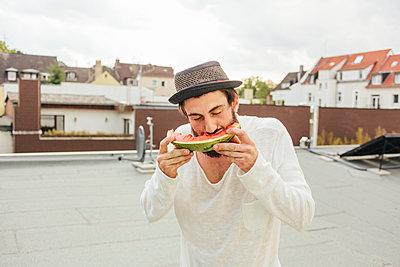 Junger Mann mit Hut und Bart isst eine Melone - p586m919112 von Kniel Synnatzschke