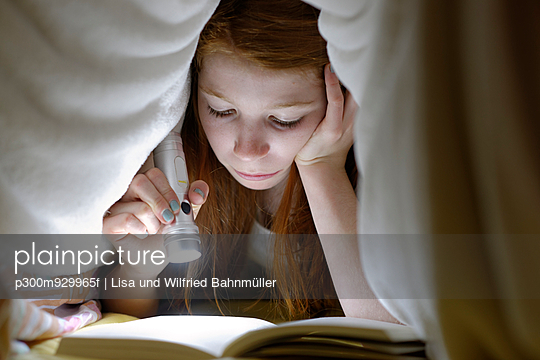 Portrait of girl reading a book secretly in bed under the blanket - p300m929965f by Lisa und Wilfried Bahnmüller
